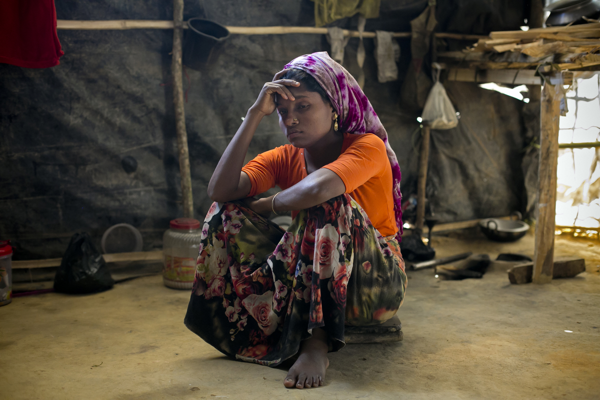 "Jamalida Begum is seen in her makeshift house that she shares with 6 other refugees on in Kutalong Rohingya refugee camp in Cox's Bazar, Bangladesh. Jamalida Begum came to Bangladesh 15 days ago from Hadgudgapara village in Myanmar. 2 months ago the military came to her village, killed her husband and burned her home to the ground with everything she owned in it. The next morning the military surrounded her village. {quote}They dragged me and the other women to the yard and beat us. I was screaming and begging Allah to save me. The military screamed {quote}Where is your Allah now? He's not saving you!""""  3 men dragged her to the bush, pointed a gun at her and said ""If you resist, I'll shoot you"" then took turns raping her until she lost consciousness. A few weeks after the rape, a group of foreign journalists came to her village and interviewed Jamalida and other rape victims. That night the military came to her village and cut the throat of the man who helped translate for the journalists. The soldiers went door to door with Jamalida's photo looking for her, and neighbors ran to warn her. She ran away and for 5 days she took shelter in the bush and in different houses until she fled to Bangladesh. She says that every night she has nightmares about the Myanmar military. {quote}I have flashbacks when I hear loud noises. I've heard that the military has made big posters of my photo and they're still going door to door looking for me. I'll never be able to go back. If I go back, they'll kill me. I will never go back. Sometimes I'm scared that they'll find me here.{quote}"