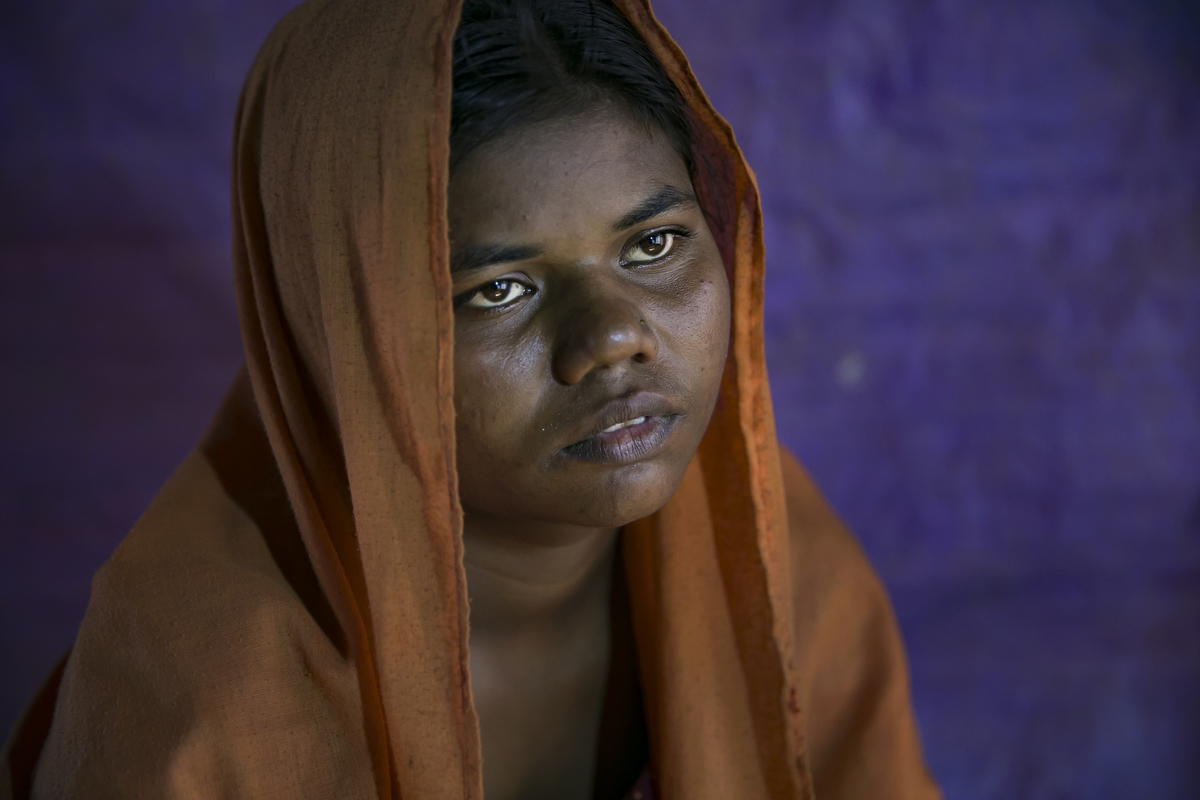 "COX'S BAZAR, BANGLADESH - DECEMBER 01: Minwara Begum, 17, poses for a photo December 1, 2017 in Cox's Bazar, Bangladesh.. She fled to Bangladesh shortly after the August 25th attack from Tula Toli village in Myanmar. One morning she was cooking when she heard shooting. Her mom went out to see what was happening and saw the military throwing petrol bombs on all the houses. {quote}All of us started running and the military shot us in the back. They shot me, my mom, sister, sister in law, nephew, 2 of my brothers. I lost 6 members of my family. I just kept on running. The military found us where we were hiding and took me, my sister and cousin and other women to a house. They tied our eyes and legs and hands with a black cloth and started to rape me. I don't know how many men raped me. There were 6 of us in the room and they killed 3 of the women. When they were finished they left the house and threw a petrol bomb on it. The whole house caught fire and I used the fire to burn the cloth off that was keeping my legs and hands tied. I tried to help the other women in the house escape, I tried to carry them, but I was too weak. I crawled out through the small chicken door and hid in a paddy field. The other 5 women in the house all burned to death."" For days she hid in the paddy field and forest until a group of other people came through and helped her. She spent days walking with them to the Bangladesh border, where she took a boat across to Bangladesh. She spent a week in a hospital in Bangladesh until she recovered. {quote}Here in Bangladesh, I feel so restless and worried. People say they're going to send us back to Myanmar, and once again they'll shoot and beat us there. I'm so worried.{quote} she says. {quote}They did these things to us, they raped us, I'm not afraid to talk about it. I don't feel ashamed to tell the world. I want justice, but I know the world cannot give me justice. If there's anyone who could give us justice, it would have happened a long time ago."" Human Rights groups have reported of widespread rape and sexual assault on Rohingya women and girls by Burmese security forces during the violence in Myanmar's Rakhine State. According to reports, more than half of the survivors of sexual assault receiving treatment by humanitarian organizations in refugee camps at the Bangladesh border are below 18 years old. The United Nations human rights chief, Zeid Ra'ad al-Hussein, said on Tuesday that Burmese security forces may be guilty of genocide against the Rohingya Muslim minority during a session in Geneva, adding international pressure on Myanmar to be investigated for crimes against humanity.(Photo by Allison Joyce/Getty Images)"