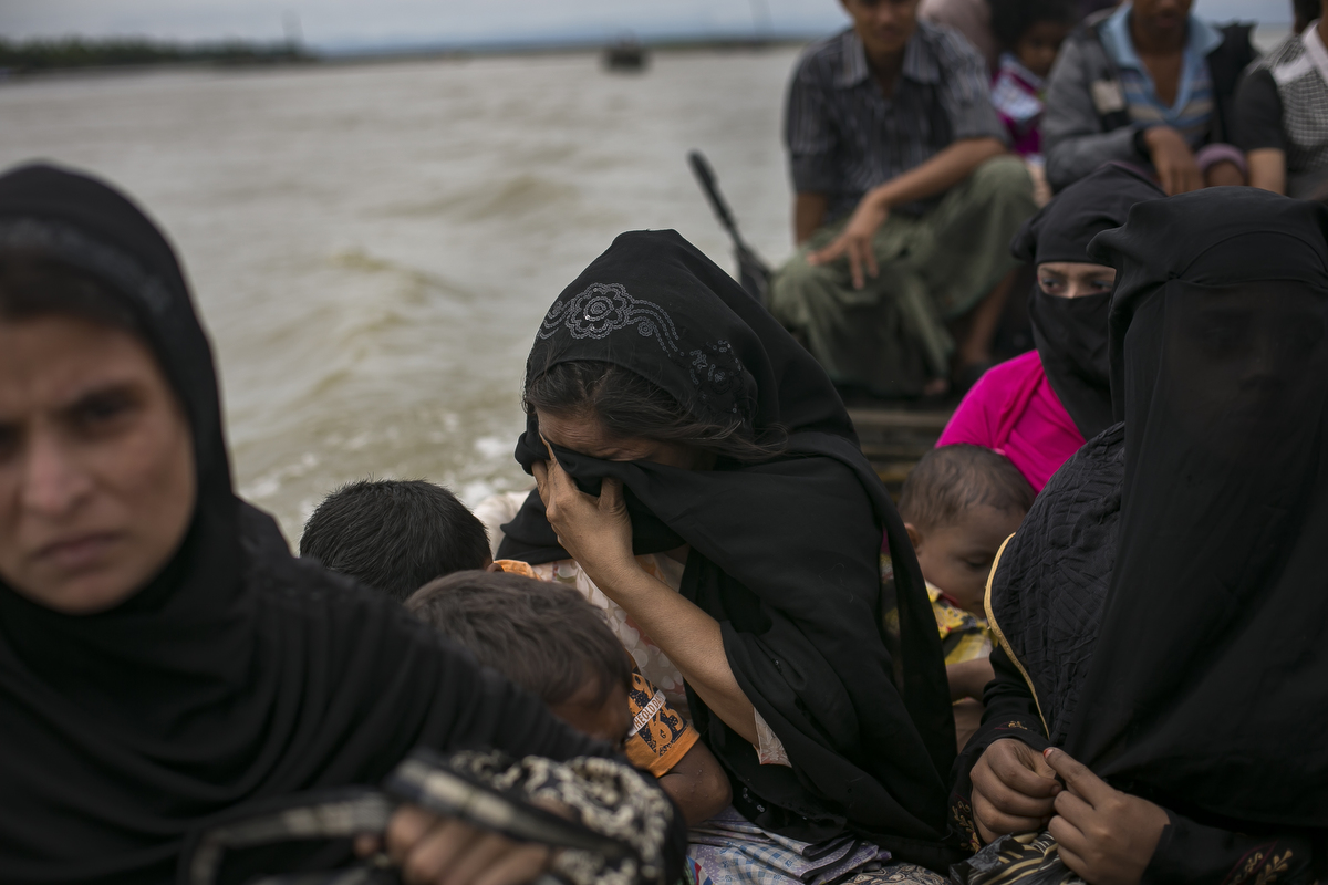 A Rohingya refugee, who's husband was killed by Burmese military, cries as she takes a boat to cross into the mainland after arriving in Bangladesh