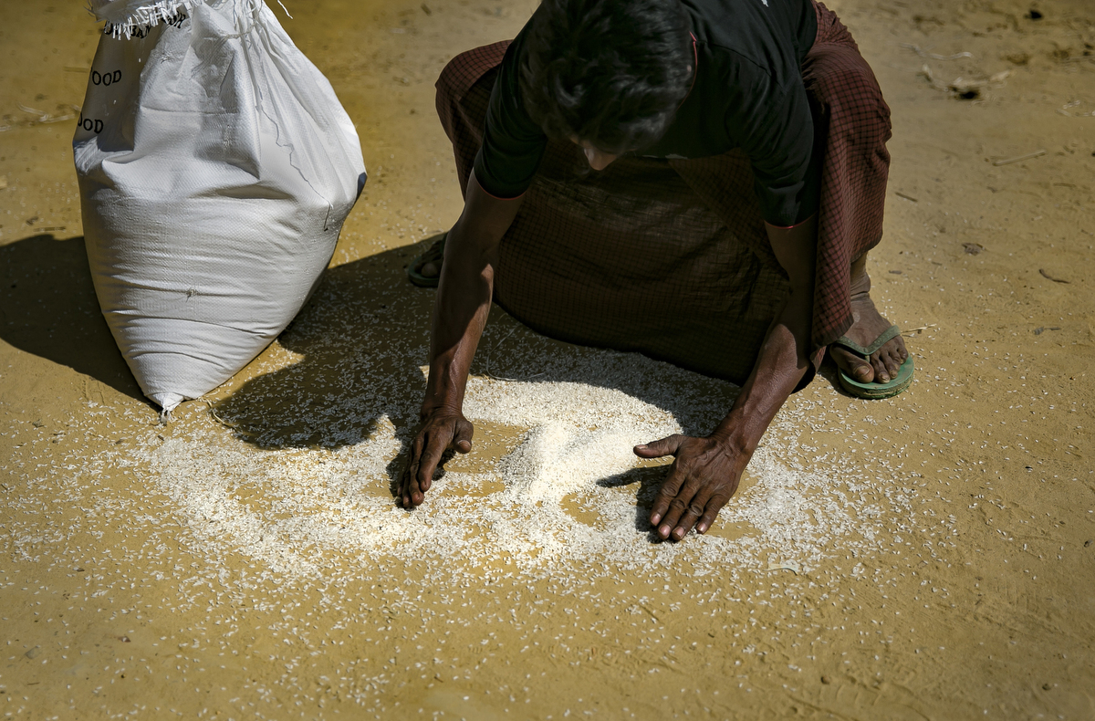 A refugee collects rice after his distribution bag broke