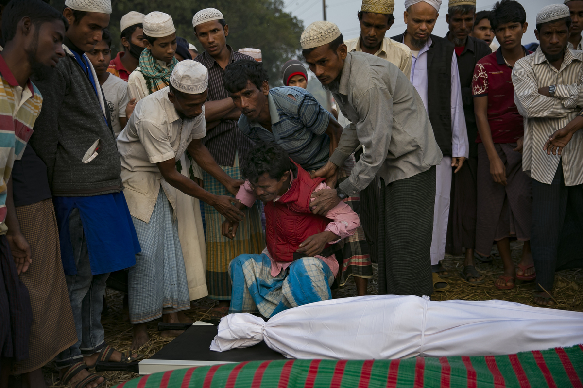 Abdul Rahim cries over the bodies of his wife and children before their burial in Balukhali camp in Cox's Bazar, Bangladesh. 30 year old Nurhaba, 8 year old Amin Sarif, 5 year old Dilsan Bibe and 1.5 year old Arjunan died in the late night of January 11th when their tent in a transit camp caught fire. Their family arrived in Bangladesh 3 days ago from Rasidong, Myanmar. They left their village 18 days ago after the Myanmar military and local Buddhist beat Nurhaba's husband, Adbul Rahim, and refused to let him harvest his fields. For 15 days they walked to the border and took shelter in other villages, with hardly enough food or water to sustain them along the way. When they were finally able to cross over into Bangladesh by boat, Abdul Rahman said they felt happy and confident about their future.