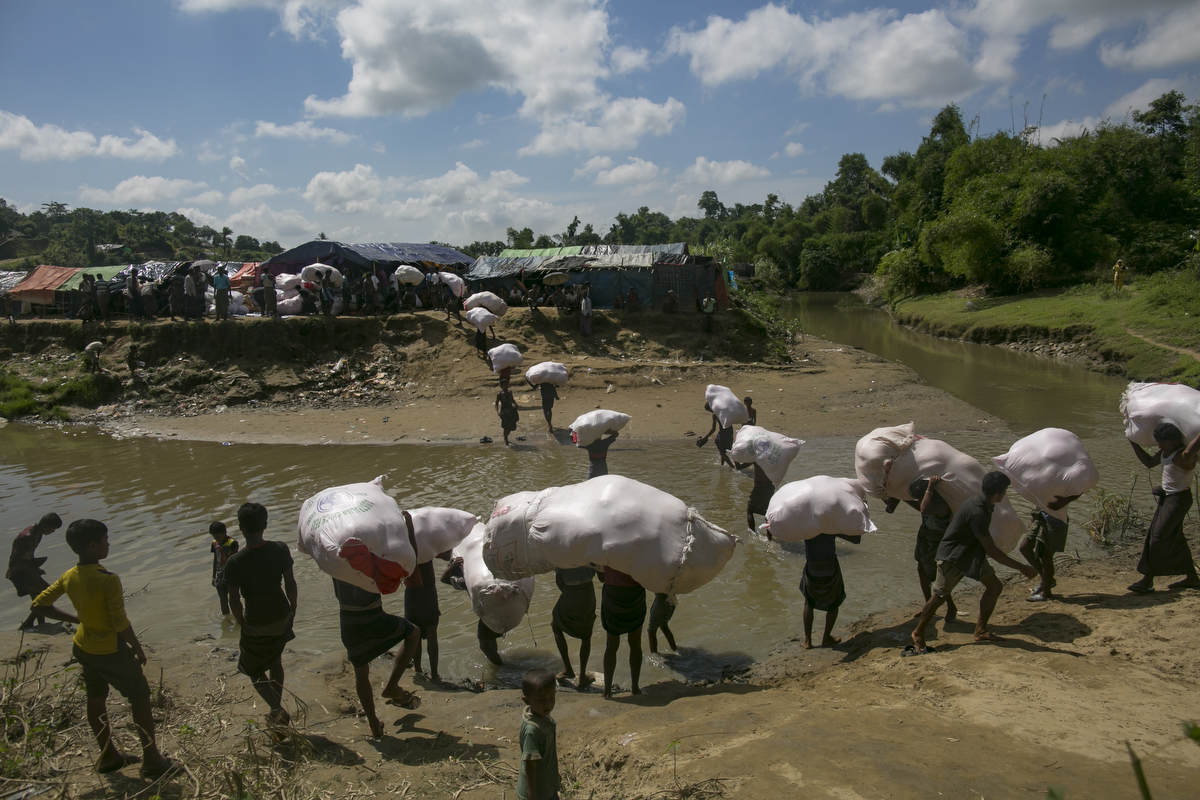 Rohingya carry donations into no man's land where Rohingya have set up refugee camps in Tombru, Bangladesh.