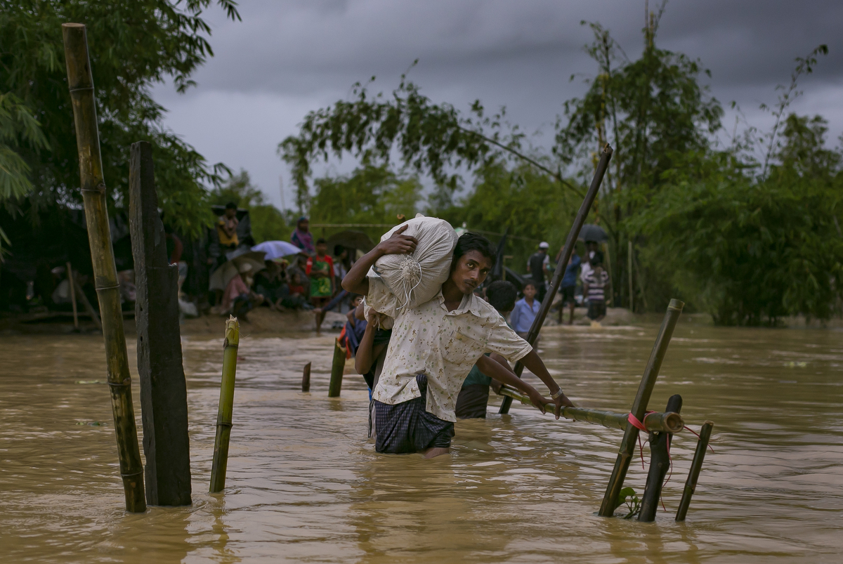 Refugees cross a flooded bridge in the Balukhali Rohingya refugee camp