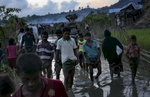 Refugees walk through a muddy path in the Unchiprang Rohingya refugee camp