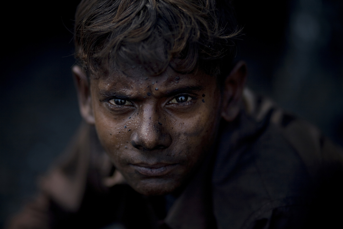 A young child collects coal illegally from local open mines in Jharia.