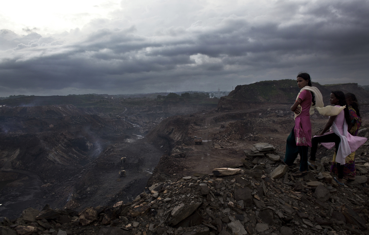 Women in the village of Bokapahari look our over a coal mine.