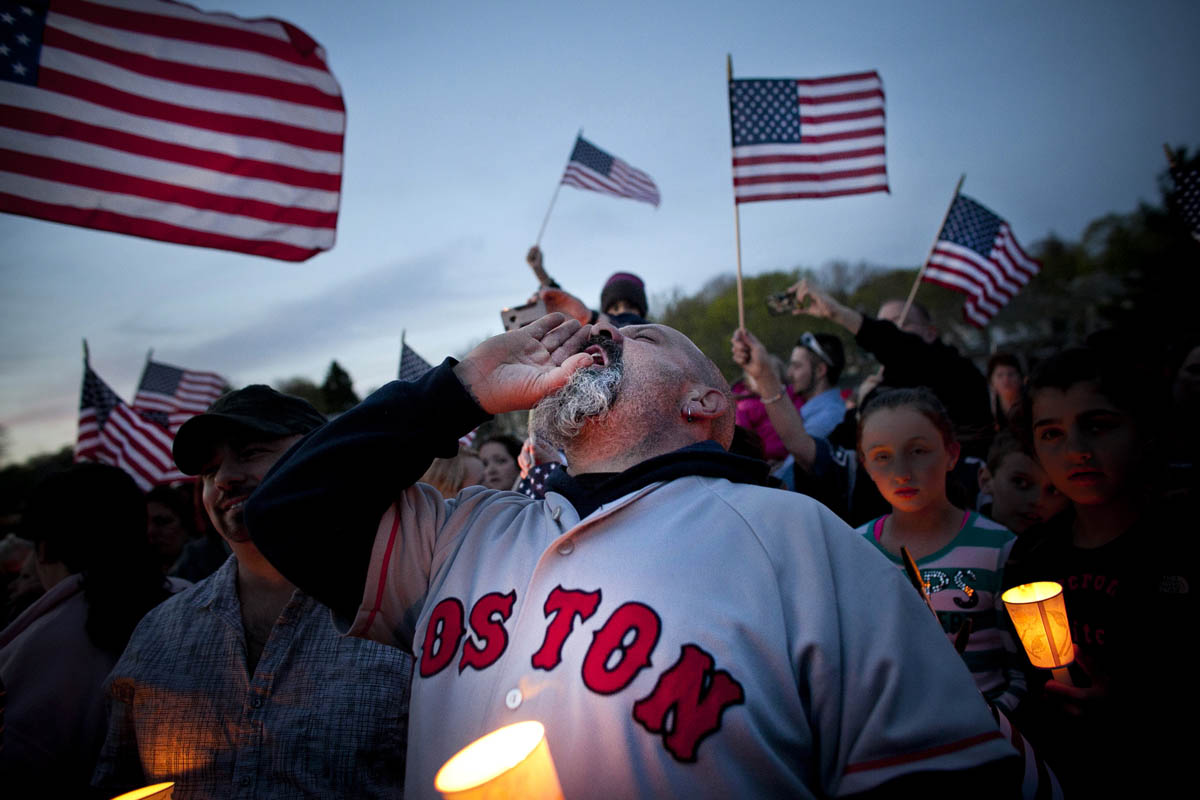 A man cheers during a candlight vigil in Watertown a day after Dzhokhar Tsarnaev was captured from a boat in a Watertown backyard.