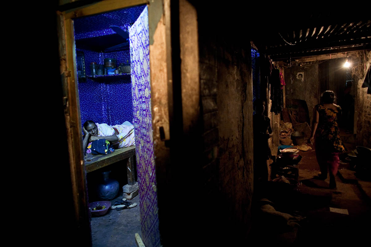 An aging sex worker reclines in her bedroom in a brothel in Faridpur, Bangladesh.