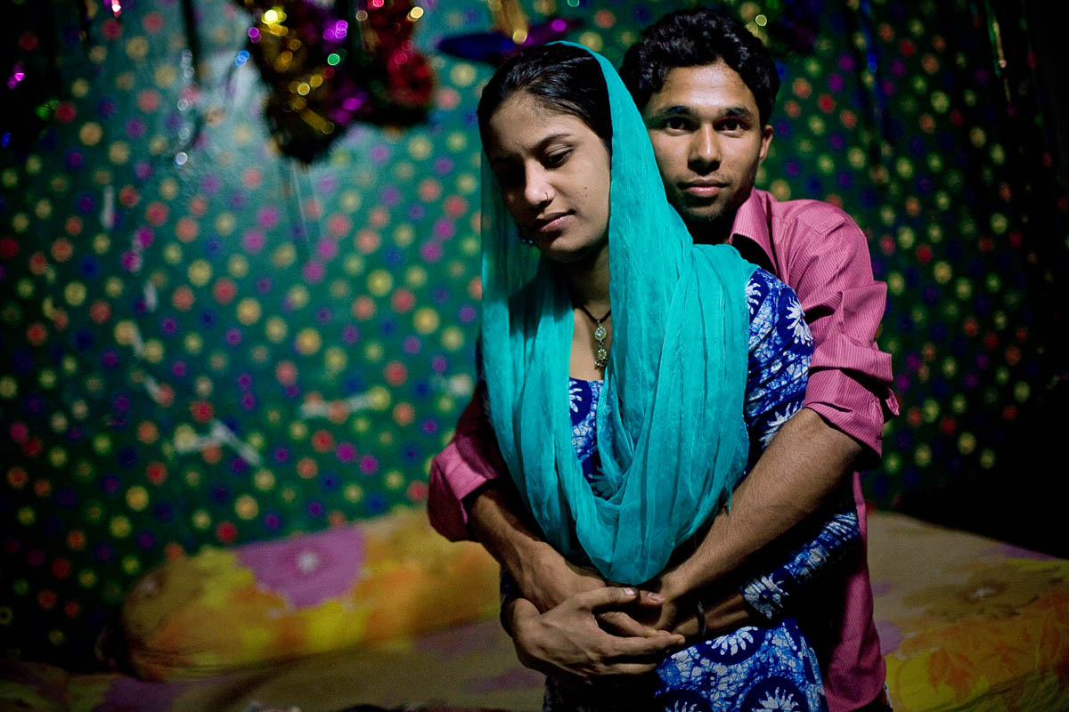 Kajul is embraced by a customer in her bedroom in a brothel in Faridpur, Bangladesh.