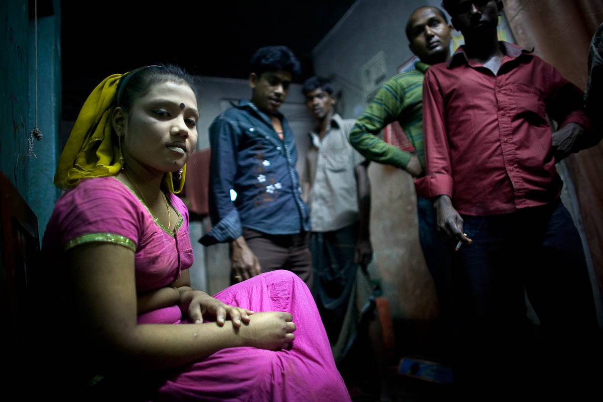 Piea waits outside her room while customers browse the halls in a brothel in Bangladesh.