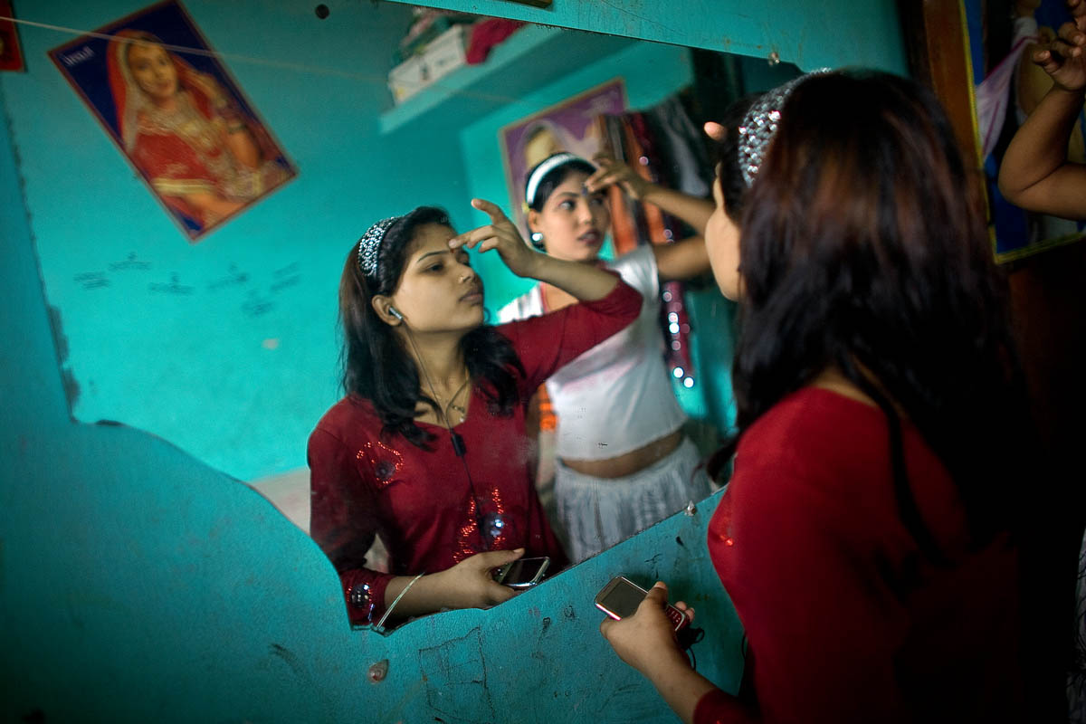 Pakhi puts on makeup before receiving customers in a brothel in Faridpur, Bangladesh. {quote}I have been working in this brothel for two years. I was married for four years but ran away because my husband was crazy. When I moved back in with my parents my uncle took me to Dhaka. I believed him when he told me he was going to enroll me in a dance school, but instead he sold me to a madame. Sometimes this place is okay, sometimes it's not, but anything is better than living with my husband. I don't talk with my parents anymore; I miss them, but  what can I do? The people in the brothel are like family to me;  Alyea (my madame) is my mother now. I love her and I dream of being a madame someday.{quote}