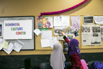 Children look at a bulletin board at the Rohingya Cultural Center of Chicago
