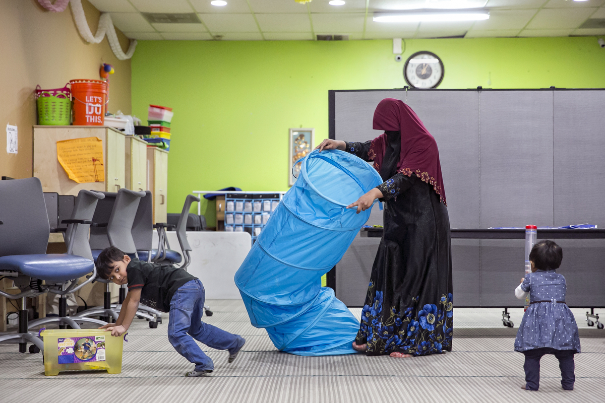 Rohingya refugee 23 year old Sakinah cleans up after English classes while her children 4 year old Shafi Rukh Khan and 1 year old Nur Sharifah play at the Rohingya Cultural Center of Chicago