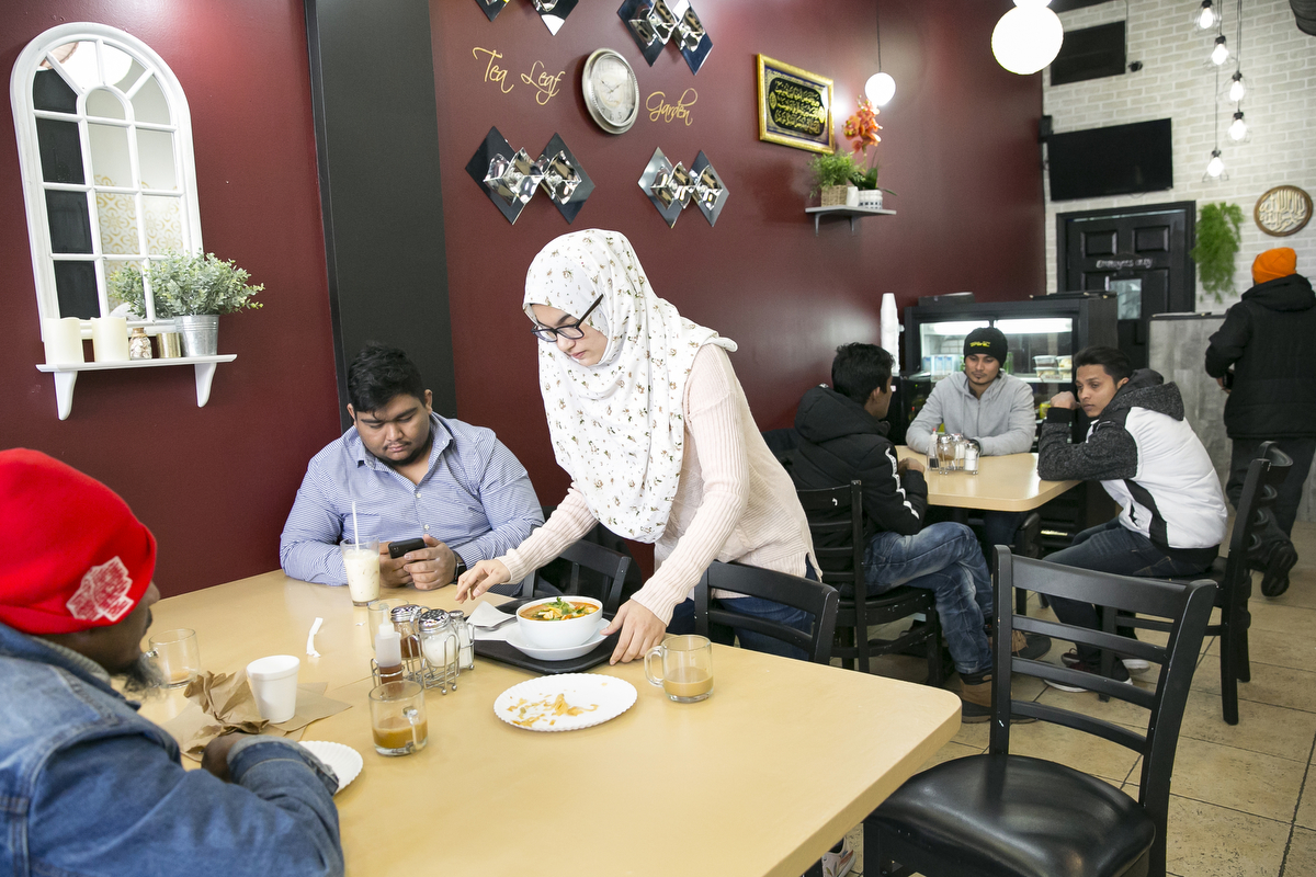 Rohingya refugee Naznin serves food at her mother's restaurant, the Tea Leaf Garden restaurant on January 11, 2019 in Chicago, Illinois. In 2018 Rohingya refugee Nasimah and her friend opened the Tea Leaf Garden restaurant, which serves halal Rohingya, Malaysian and Burmese food. Nasimah escaped violence and oppression in Myanmar in 1977 to Malaysia and was resettled with her family in Chicago in 2012. Her son Mohammad says that {quote}Everything is better here in the US. We are able to go to school.{quote}