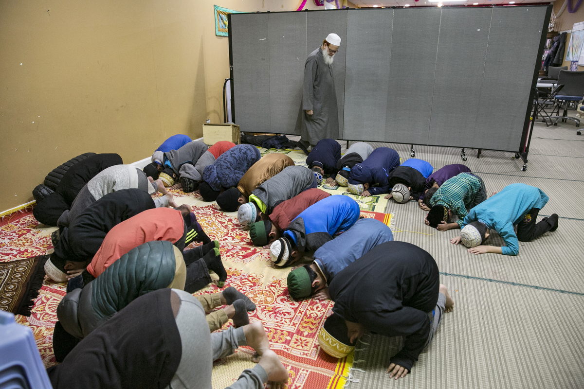 Children pray at the Rohingya Cultural Center of Chicago