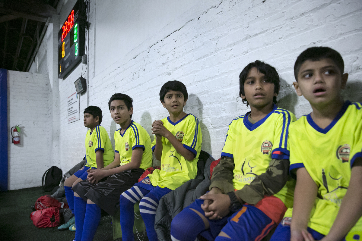 The Rohingya Cultural Center of Chicago soccer team watches teammates during a game
