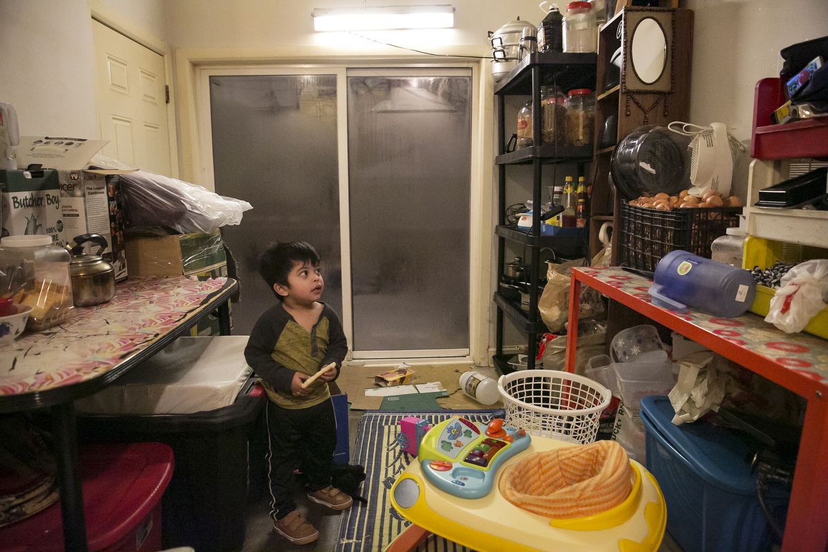 2 year old Amirul watches TV on a phone while his mother cooks dinner on January 12, 2019 in Chicago, Illinois. The Shukor family arrived in Chicago in 2014 from Malaysia. Mohammad Shukor fled Myanmar in 1978 after the military shot him and arrested his father, who died in jail. He fled to Thailand by boat and spent 5 years there before making his way to Malaysia with his family. In Malaysia he and his family were denied an education, had to work illegally, and were frequently arrested and harassed by authorities. When he and his family were resettled in the US he says he {quote}felt so happy to finally have a country, to finally have a place to call home{quote}.