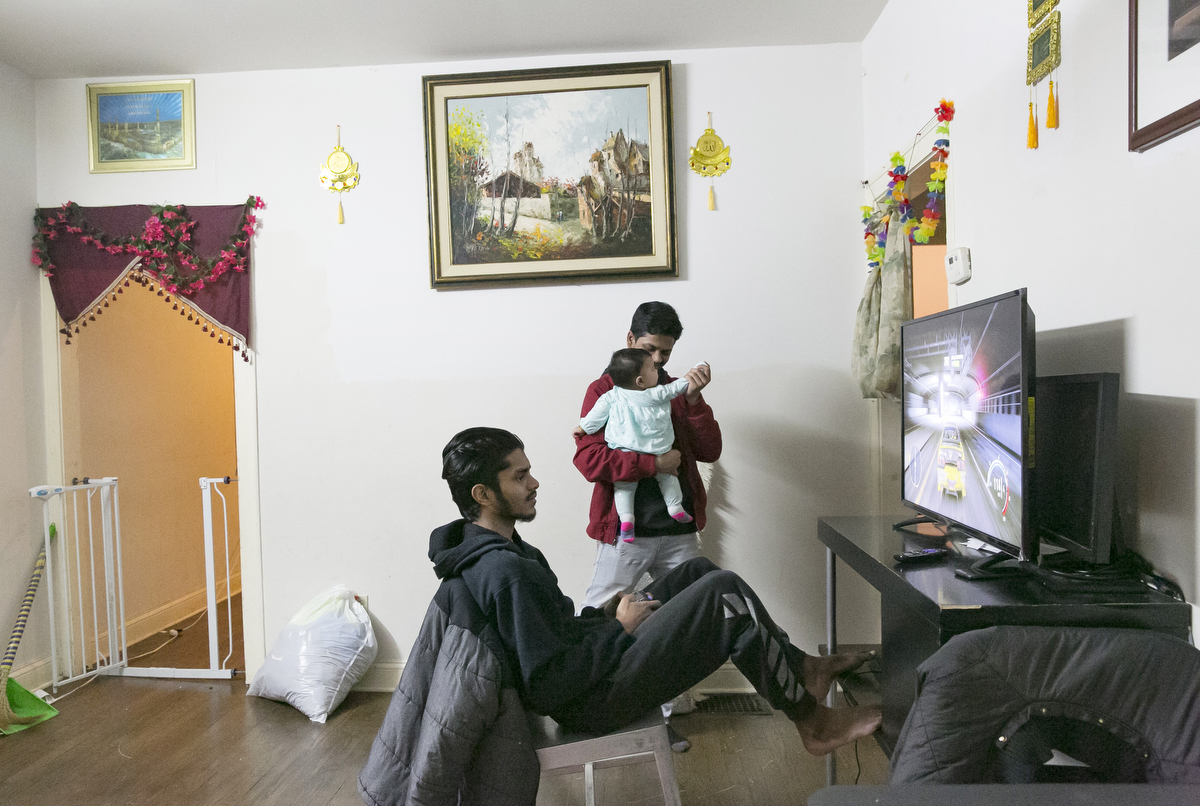 Feroz Shukor plays video games in his home on January 12, 2019 in Chicago, Illinois. The Shukor family arrived in Chicago in 2014 from Malaysia. Mohammad Shukor fled Myanmar in 1978 after the military shot him and arrested his father, who died in jail. He fled to Thailand by boat and spent 5 years there before making his way to Malaysia with his family. In Malaysia he and his family were denied an education, had to work illegally, and were frequently arrested and harassed by authorities. When he and his family were resettled in the US he says he {quote}felt so happy to finally have a country, to finally have a place to call home{quote}.