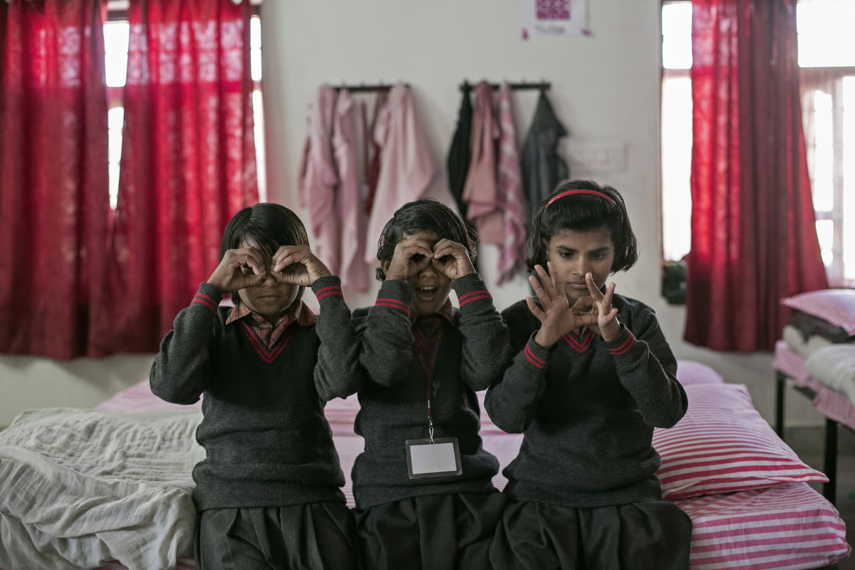 Priyanka, 11, (right red headband) plays with her friends before school at the Veerni Institute