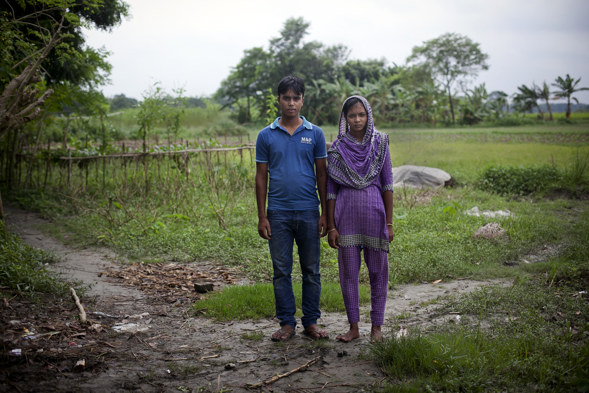 27 year old Mohammad Sujon Mia stands for a photo beside his wife, 14 year old Mousammat Akhi Akhter. Last year, when she was only 13, Akhi got married a 27 year old man. She had finished 6th grade and wanted to wait until she was older to get married, but she says her parents felt social pressure to marry her young.