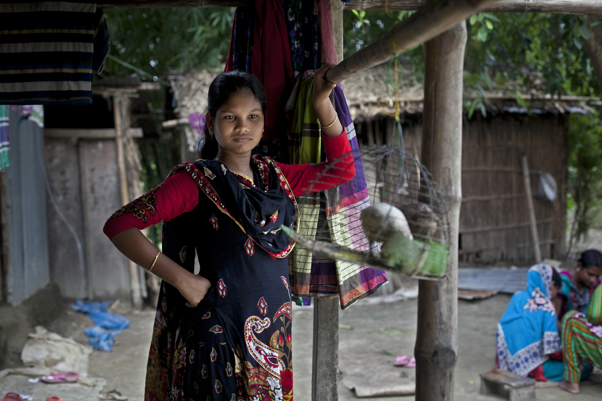 14 year old Shima Akhter stands on the front porch of her home August 19, 2015 in Manikganj, Bangladesh. Last year, when she was 13, Shima married an 18 year old man.