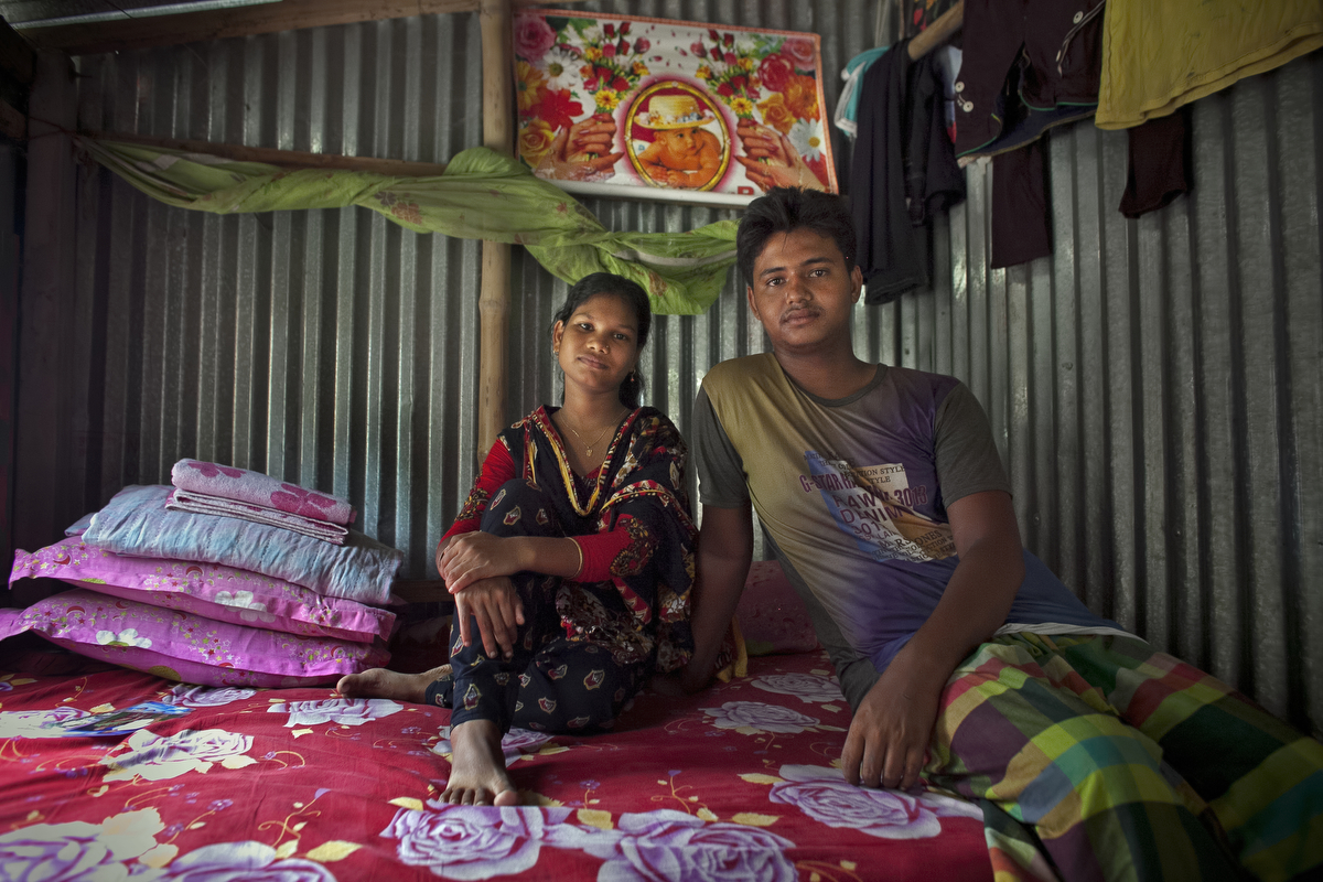 14 year old Shima Akhter poses for a photo with her husband, 18 year old Mohammad Solaiman in their home. Last year, when she was 13, Shima married her 18 year old husband.