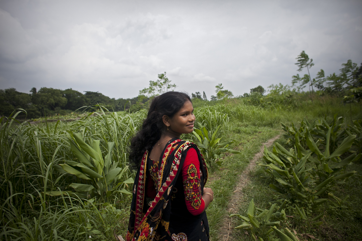 14 year old Shima Akhter walks through a field near her home. Last year, when she was 13, Shima married an 18 year old man.
