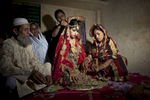 15 year old Nasoin Akhter sits with relatives while posing for photos on the day of her wedding to a 32 year old man,