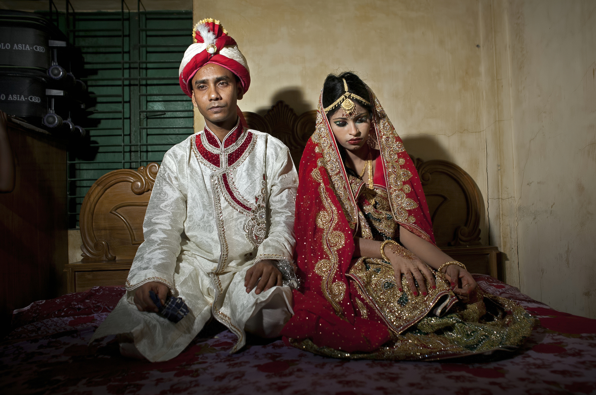 32 year old Mohammad Hasamur Rahman poses for photographs with his new 15 year old bride
