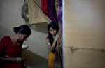 15 year old Nasoin Akhter looks out of a dressing room at a beauty parlour on the day of her wedding to a 32 year old man,