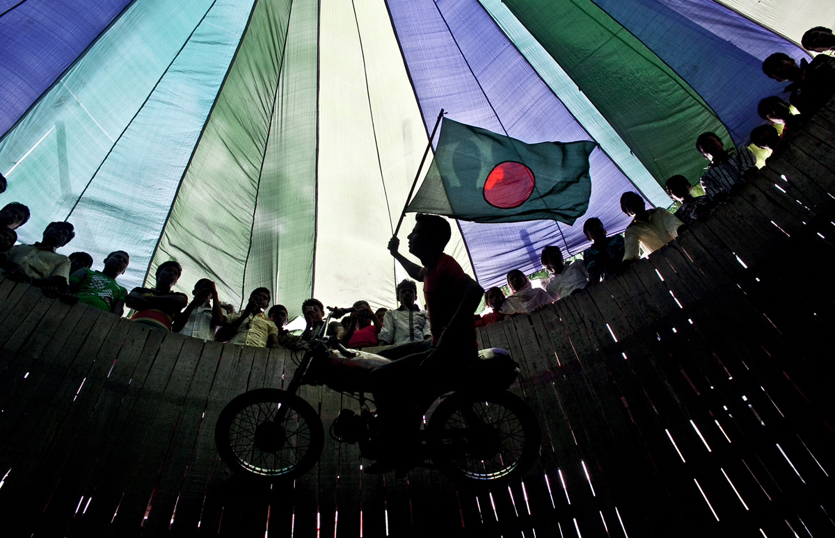 A man flies the Bangladesh flag as he rides a motorcycle in Dhamrai, Bangladesh.