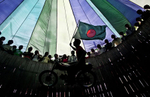 A man flies the Bangladesh flag as he rides a motorcycle in Dhamrai, Bangladesh.