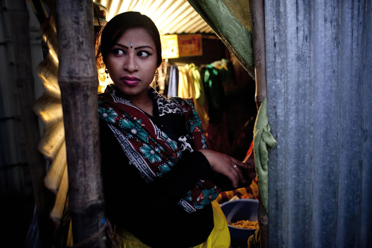16 year old Bristi Akhter looks out from her makeshift home in the residential area behind the Olympic Circus. Bristi, was born into the circus. She dropped out of school when she was 14 years old to start performing and got married to her cousin last month,