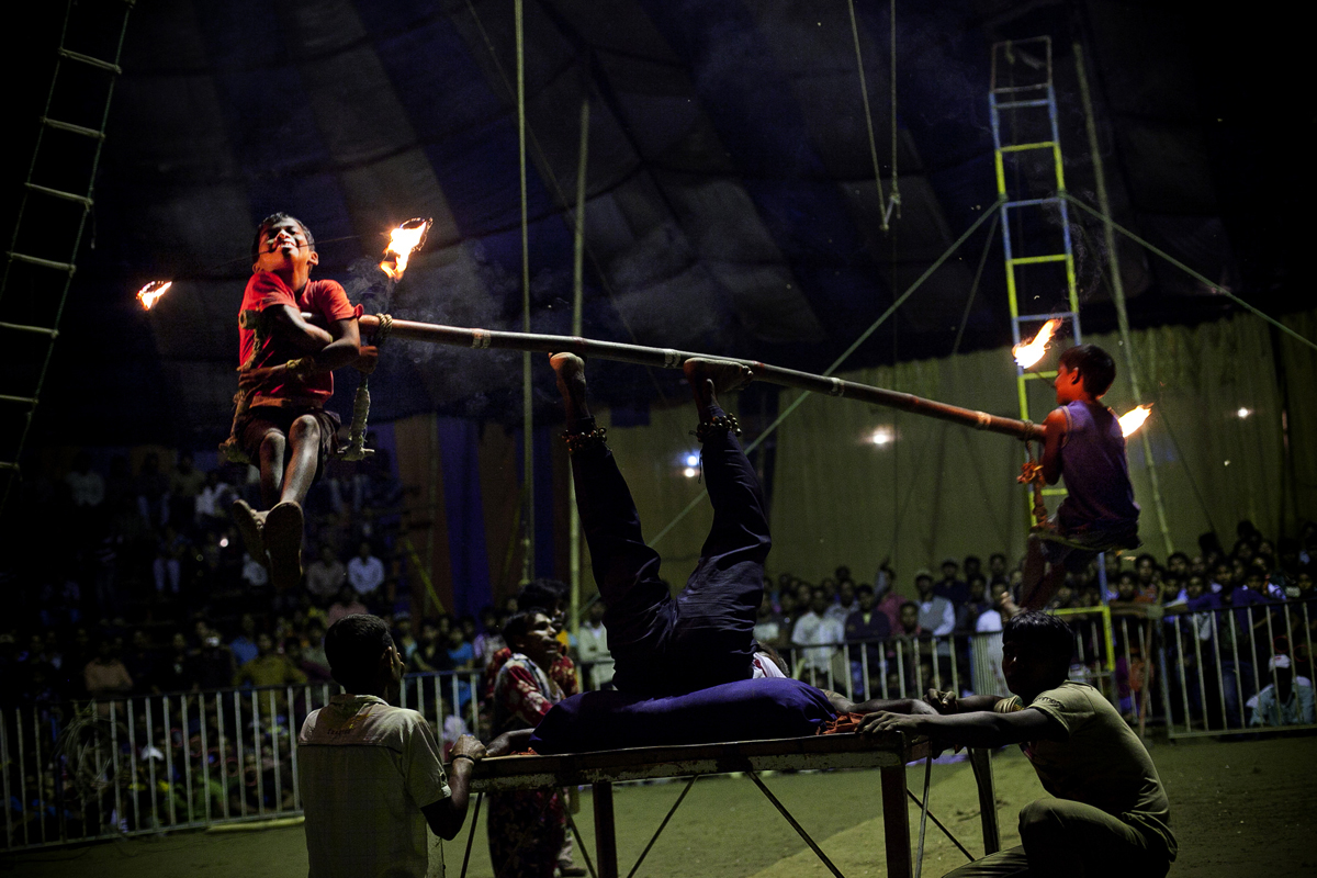 11 year old Sharif and 7 year old Nishan hold flaming sticks in their mouth as their father Mohammad Moshroom spins them on a pole during a performance at the Olympic Circus.