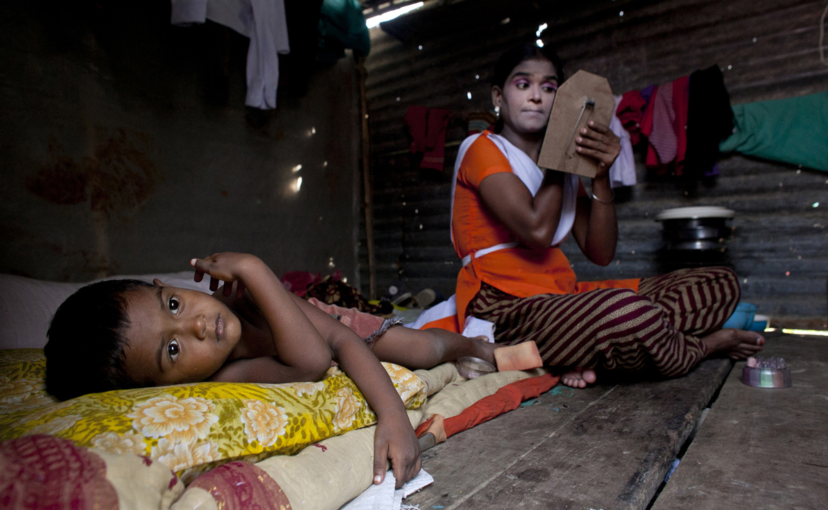 Baby Akhter Sultang applies makeup as her 3 year old son, Shobujh, lays on their bed at the Olympic Circus. Baby, who doesn't know her age, grew up in the circus without ever having the chance to attend school. She has been performing for 6 years, does not enjoy performing but says she stays because she needs the money.