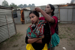 (L-R)16 year old Bristi Akhter has her hair checked for bugs by her mother, Sheuliy, in the residential area behind the Olympic Circus. She got married to her cousin last month, and she dropped out of school when she was 14 years old to start performing. Sheuliy, who doesn't know her age, got married to another circus worker when she was 10 or 11 years old. She never had a chance to go to school.