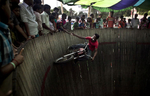 A man collects tips the as he rides a motorcycle  at a circus in Dhamrai, Bangladesh.