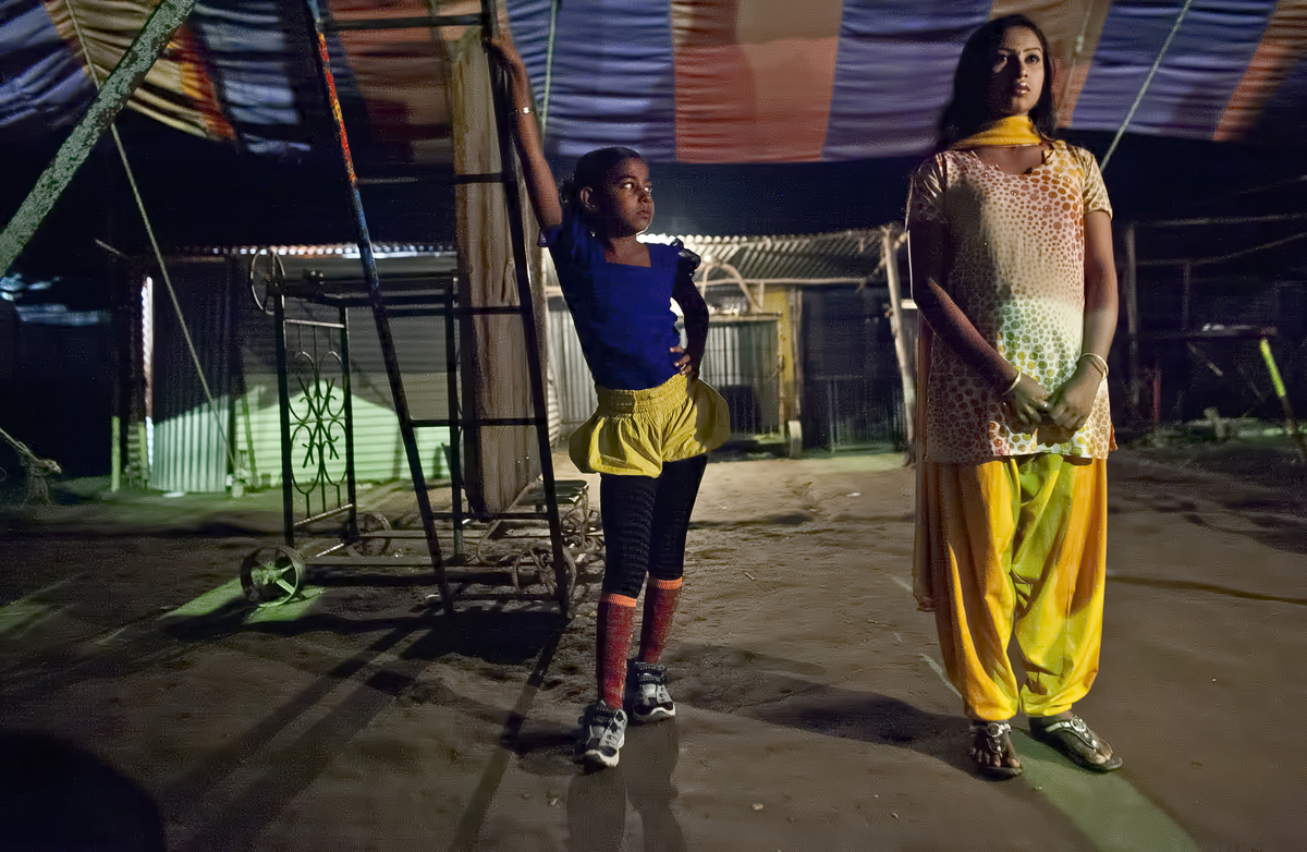 8 year old Puja Sarker looks at an older circus worker before she performs at the Olympic Circus. Puja was born into the circus, as were her parents, and never had the chance to attend school.