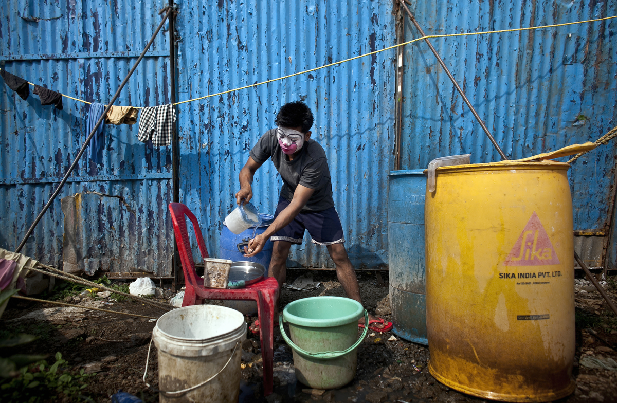 A clown washes dishes before a show at the Rambo Circus in Pimpri, India.