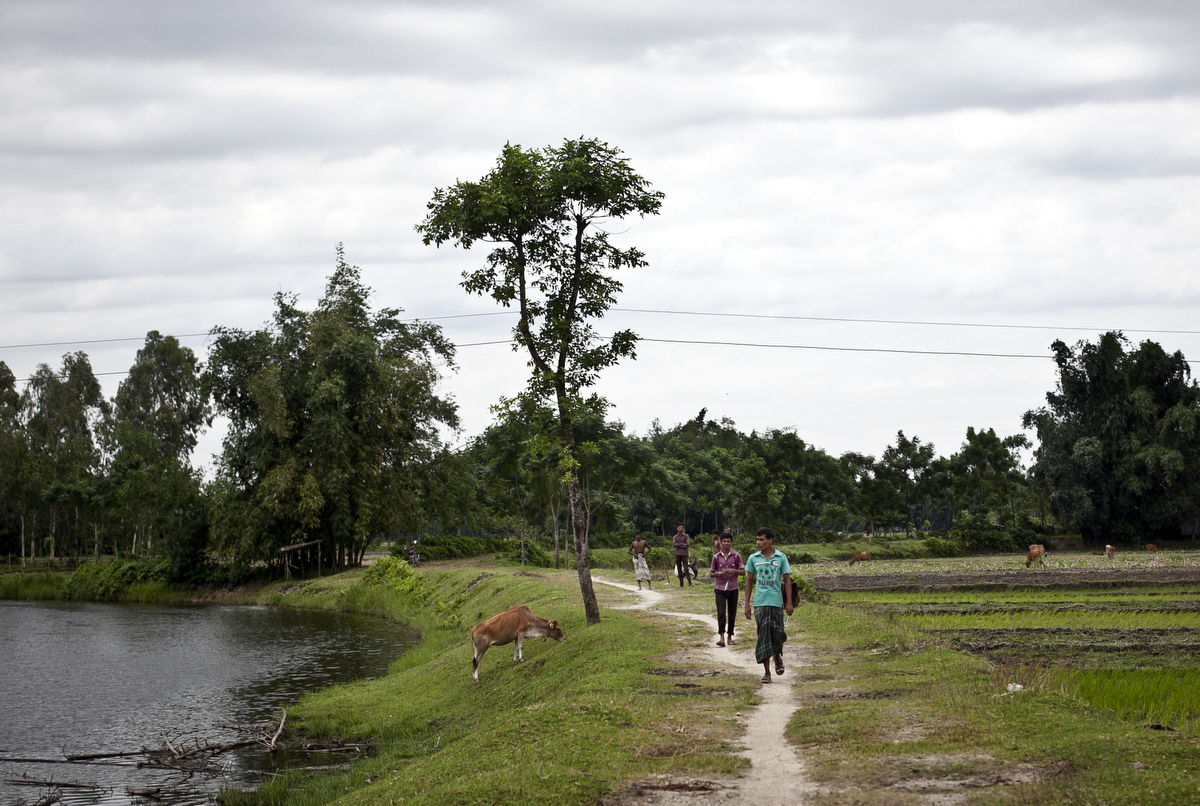 People walk from the Bash Kata Indian enclave into Bangladesh in Lalmonirhat District, Bangladesh.