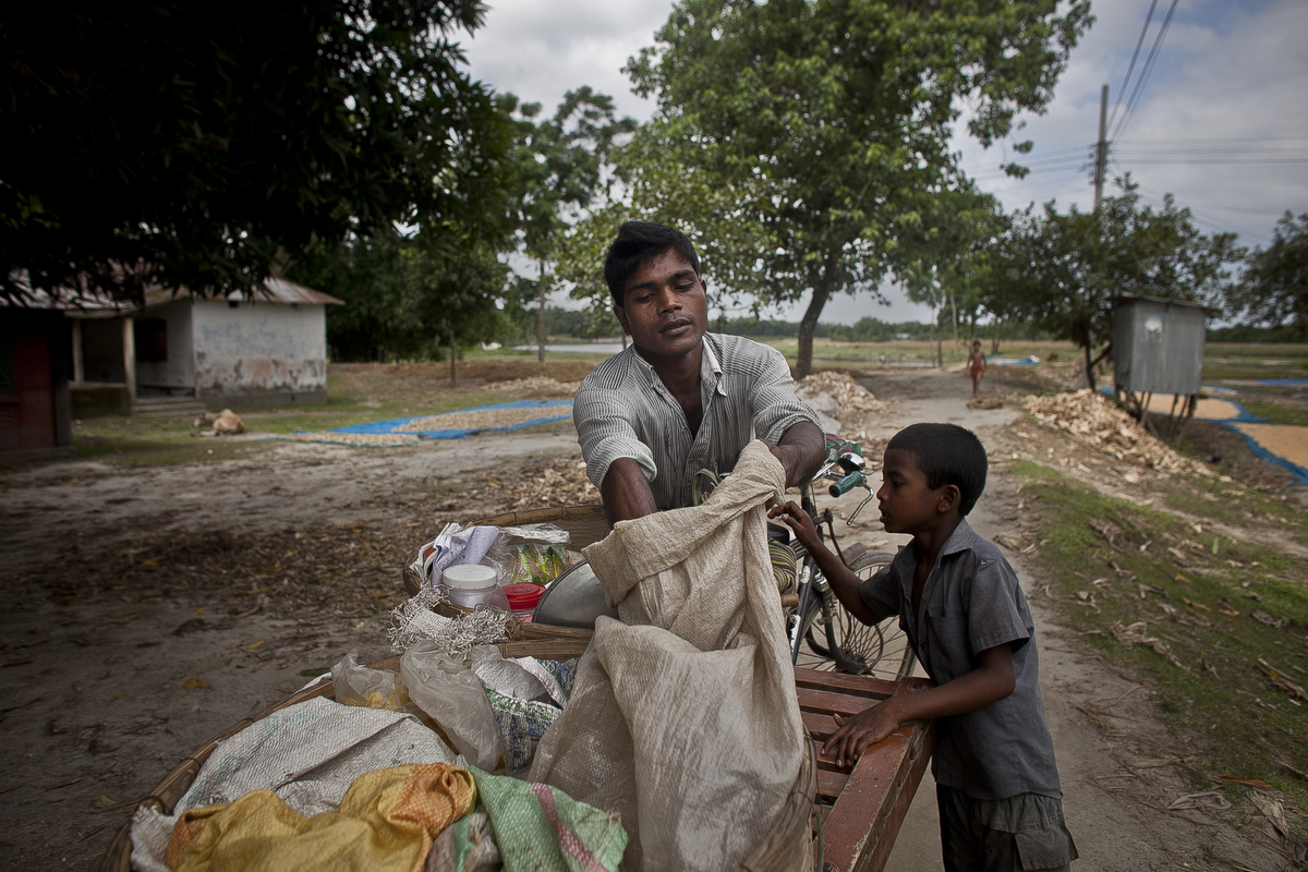 A child buys rice from a mobile vendor in the Bash Kata Indian enclave in Lalmonirhat District, Bangladesh.