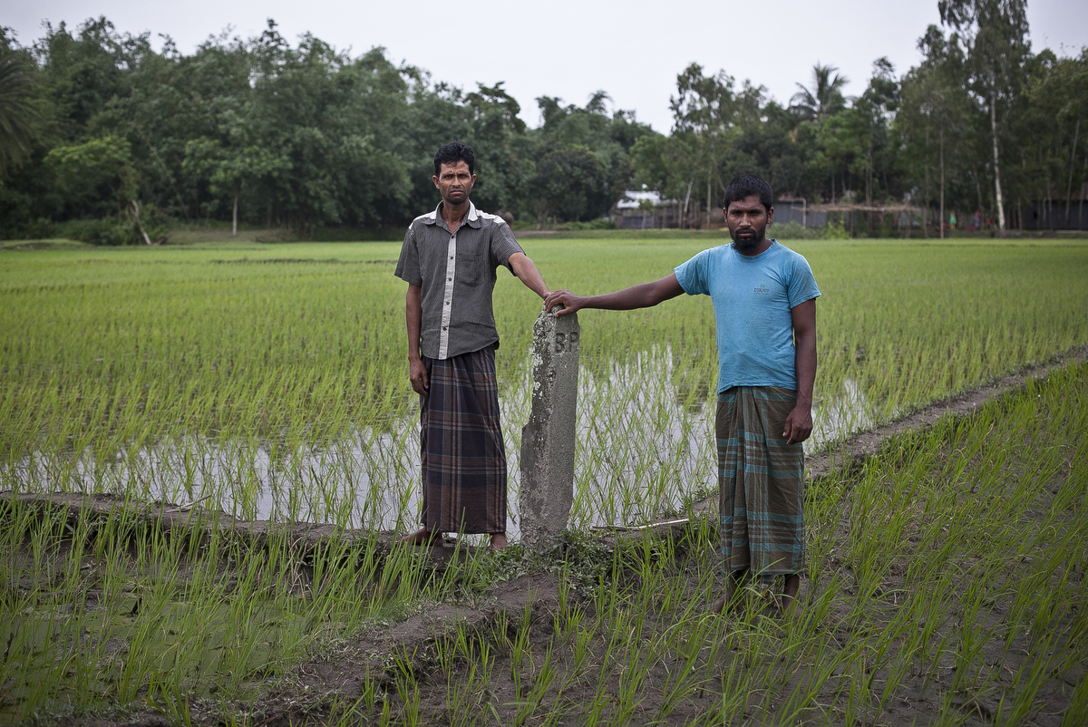 Bagdakia Indian enclave resident Mohammad Anwar Hossain (left) stands in Indian territory while Bangladeshi citizen Mohammar Monwar Hossain (right) stands in Bangladesh territory in Lalmonirhat District, Bangladesh.