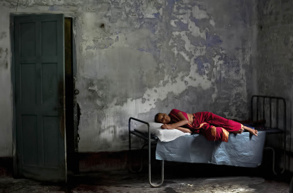 A patient lies on a bed in Pabna Mental Hospital August 19, 2014 in Pabna, Bangladesh. Mental health in Bangladesh is largely neglected and under financed, and the stigma of mental health is huge. In rural areas there are few doctors and families generally take the patient to a traditional healer first, who usually tries to exorcize the Jinn (spirits) with holy water and versus from the Koran. Families who have a mentally ill family member sometimes tie them up out of desperation and lack of education and options. There is only one government run mental hospital with 500 beds in the entire country. Less than 0.5% of government health budget is spent for mental health. Allison Joyce/Redux