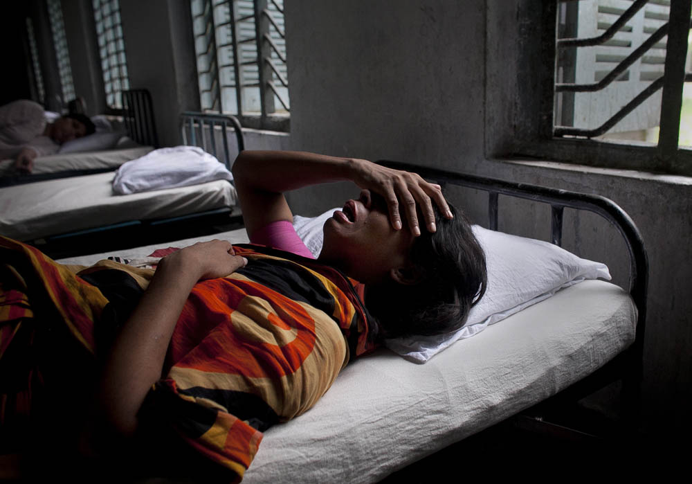 A patient cries as she lies on her bed in Pabna Mental Hospital August 19, 2014 in Pabna, Bangladesh. Mental health in Bangladesh is largely neglected and under financed, and the stigma of mental health is huge. In rural areas there are few doctors and families generally take the patient to a traditional healer first, who usually tries to exorcize the Jinn (spirits) with holy water and versus from the Koran. Families who have a mentally ill family member sometimes tie them up out of desperation and lack of education and options. There is only one government run mental hospital with 500 beds in the entire country. Less than 0.5% of government health budget is spent for mental health. Allison Joyce/Redux