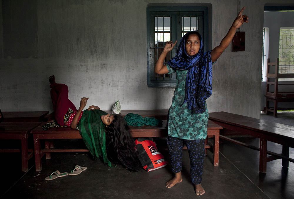 35 year old patient Barvine Akhter (right) and another patient are seen at the intake center of Pabna Mental Hospital August 21, 2014 in Pabna, Bangladesh. Mental health in Bangladesh is largely neglected and under financed, and the stigma of mental health is huge. In rural areas there are few doctors and families generally take the patient to a traditional healer first, who usually tries to exorcize the Jinn (spirits) with holy water and versus from the Koran. Families who have a mentally ill family member sometimes tie them up out of desperation and lack of education and options. There is only one government run mental hospital with 500 beds in the entire country. Less than 0.5% of government health budget is spent for mental health. Allison Joyce/Redux