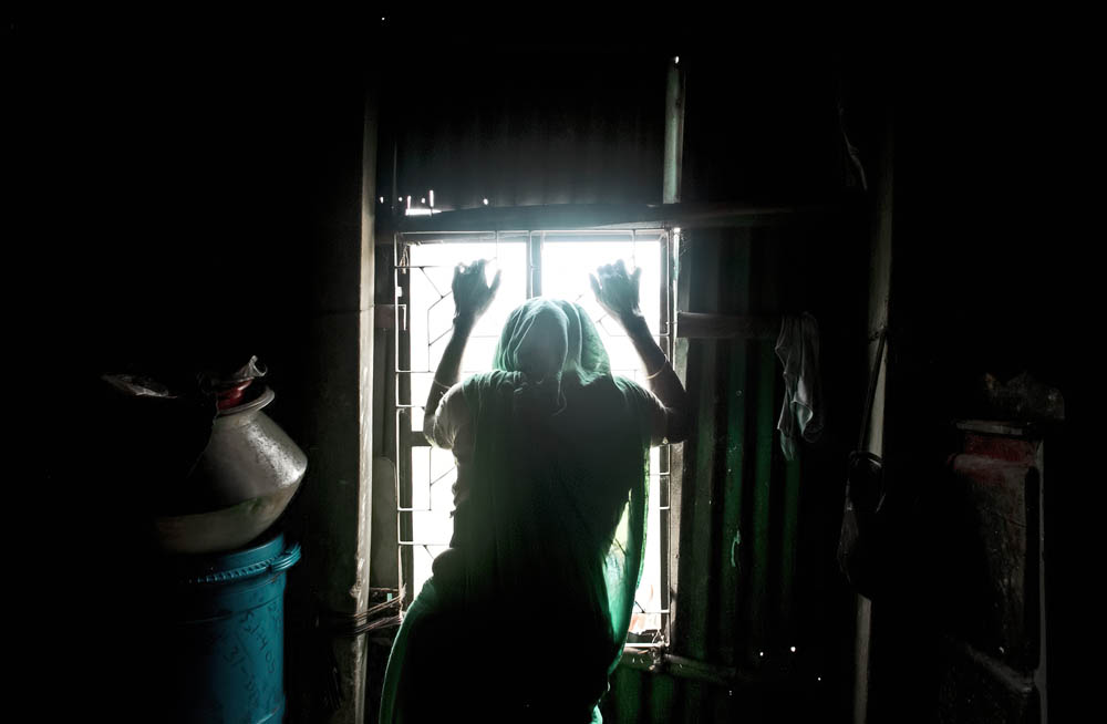 Widow Samira Begum, who cares for her mentally ill son, 22 year old Rofikul, looks out the window of her home August 23, 2014 in Pabna, Bangladesh. Rofikul is unable to speak and often gets violent, but doctors at Pabna Mental Hospital certified him mentally fit and discharged him. His family occasionally chains him because he runs away into town and becomes violent with people, and they feel that  they have no other options. Mental health in Bangladesh is largely neglected and under financed, and the stigma of mental health is huge. In rural areas there are few doctors and families generally take the patient to a traditional healer first, who usually tries to exorcize the Jinn (spirits) with holy water and versus from the Koran. Families who have a mentally ill family member sometimes tie them up out of desperation and lack of education and options. There is only one government run mental hospital with 500 beds in the entire country. Less than 0.5% of government health budget is spent for mental health. Allison Joyce/Redux