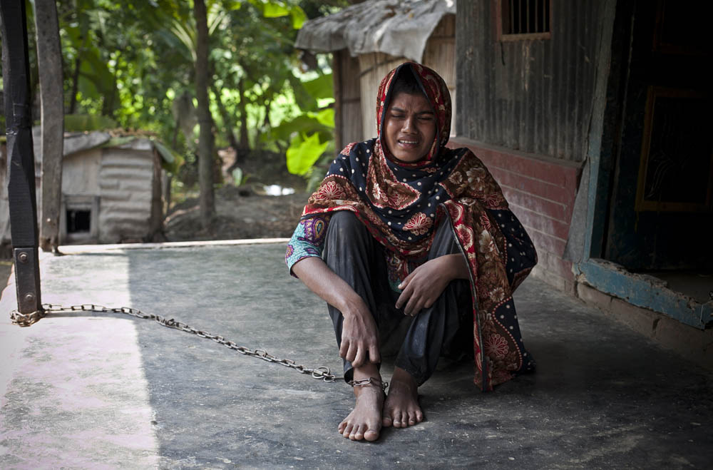 16 year old schizophrenic Tara Banu sits chained to her front porch August 24, 2014 in Pabna, Bangladesh. She tried to commit suicide by hanging herself 2 years ago and her family says she has been mentally disturbed since then. She spent 5 1/2 months at Pabna Mental Hospital where she was diagnosed with schizophrenia, and the doctors recently discharged her and sent her home telling her family that she was cured. Her family chains her because she frequently tries to run away and harm herself, and they feel that they have no other options. Mental health in Bangladesh is largely neglected and under financed, and the stigma of mental health is huge. In rural areas there are few doctors and families generally take the patient to a traditional healer first, who usually tries to exorcize the Jinn (spirits) with holy water and versus from the Koran. Families who have a mentally ill family member sometimes tie them up out of desperation and lack of education and options. There is only one government run mental hospital with 500 beds in the entire country. Less than 0.5% of government health budget is spent for mental health. Allison Joyce/Redux