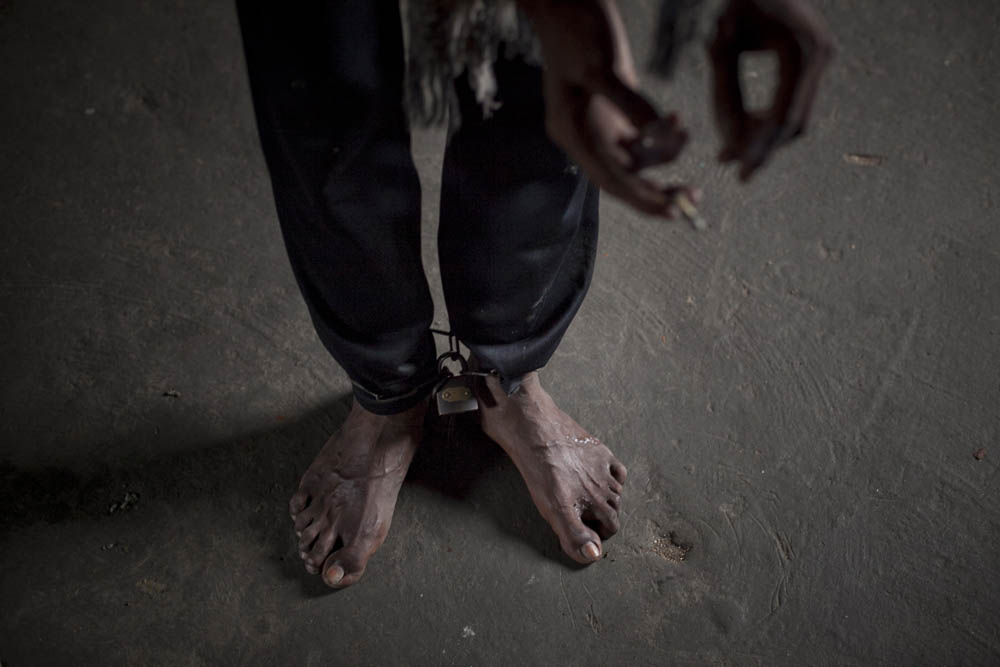 Mentally ill 22 year old Rofikul smokes a cigarette while his legs are chained August 23, 2014 in Pabna, Bangladesh. Rofikul is unable to speak and often gets violent, but doctors at Pabna Mental Hospital certified him mentally fit and discharged him. His family occasionally chains him because he runs away into town and becomes violent with people, and they feel that  they have no other options. Mental health in Bangladesh is largely neglected and under financed, and the stigma of mental health is huge. In rural areas there are few doctors and families generally take the patient to a traditional healer first, who usually tries to exorcize the Jinn (spirits) with holy water and versus from the Koran. Families who have a mentally ill family member sometimes tie them up out of desperation and lack of education and options. There is only one government run mental hospital with 500 beds in the entire country. Less than 0.5% of government health budget is spent for mental health. Allison Joyce/Redux