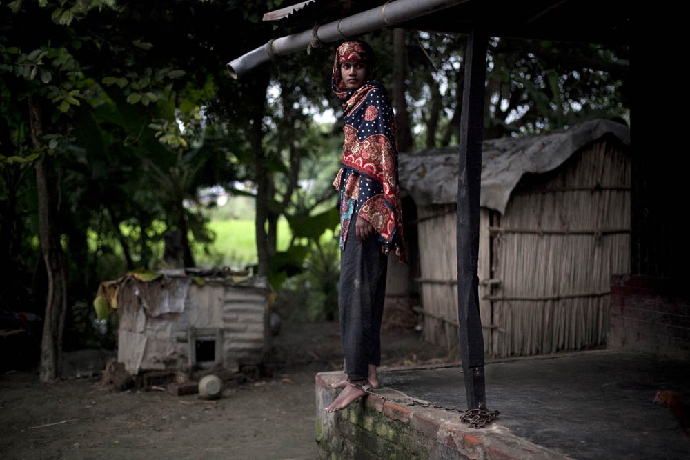 16 year old schizophrenic Tara Banu stands chained to her front porch August 24, 2014 in Pabna, Bangladesh. She tried to commit suicide by hanging herself 2 years ago and her family says she has been mentally disturbed since then. She spent 5 1/2 months at Pabna Mental Hospital where she was diagnosed with schizophrenia, and the doctors recently discharged her and sent her home telling her family that she was cured. Her family chains her because she frequently tries to run away and harm herself, and they feel that they have no other options. Mental health in Bangladesh is largely neglected and under financed, and the stigma of mental health is huge. In rural areas there are few doctors and families generally take the patient to a traditional healer first, who usually tries to exorcize the Jinn (spirits) with holy water and versus from the Koran. Families who have a mentally ill family member sometimes tie them up out of desperation and lack of education and options. There is only one government run mental hospital with 500 beds in the entire country. Less than 0.5% of government health budget is spent for mental health. Allison Joyce/Redux