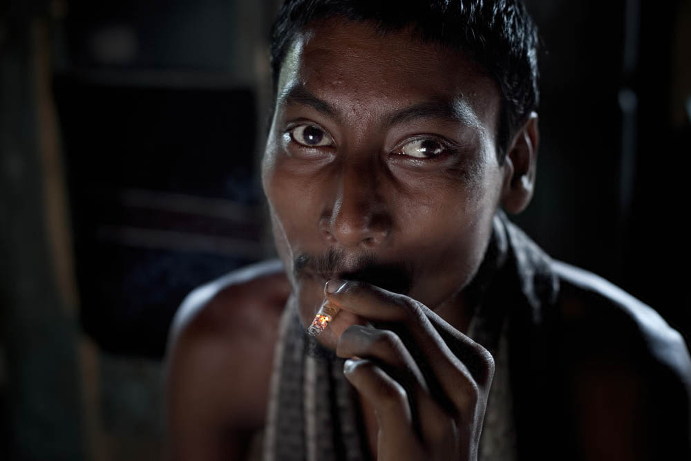 Mentally ill 22 year old Rofikul smokes a cigarette August 25, 2014 in Pabna, Bangladesh. Rofikul is unable to speak and often gets violent, but doctors at Pabna Mental Hospital certified him mentally fit and discharged him. His family occasionally chains him because he runs away into town and becomes violent with people, and they feel that  they have no other options. Mental health in Bangladesh is largely neglected and under financed, and the stigma of mental health is huge. In rural areas there are few doctors and families generally take the patient to a traditional healer first, who usually tries to exorcize the Jinn (spirits) with holy water and versus from the Koran. Families who have a mentally ill family member sometimes tie them up out of desperation and lack of education and options. There is only one government run mental hospital with 500 beds in the entire country. Less than 0.5% of government health budget is spent for mental health. Allison Joyce/Redux